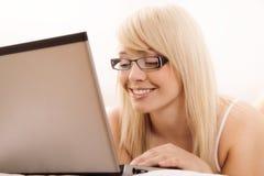 Internet da consultação da jovem mulher Imagens de Stock