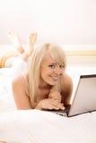 Internet da consultação da jovem mulher Imagem de Stock