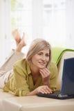 Internet da consultação da mulher em casa foto de stock