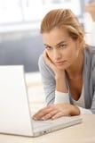 Internet da consultação da mulher nova Fotografia de Stock