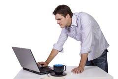 Internet da consultação do homem novo no portátil Foto de Stock Royalty Free