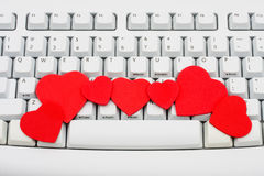 Internet Dating. Red hearts sitting on a computer keyboard, internet dating Stock Photo