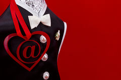 Internet dating. Concept shot.At symbol inside of a red heart shape and black man suit on a red background.  Image blank with copy space Stock Photography