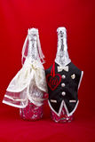 Internet dating or wedding. Concept shot.At symbol inside of a red heart shape with a bottles of champagne dressed in a black man suit and wedding dress on a royalty free stock images