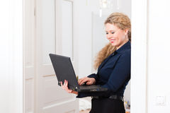 Internet Dating - Woman at home after work. Online Dating - Young businesswoman at home while using a laptop computer, for dating or reading emails Royalty Free Stock Photography