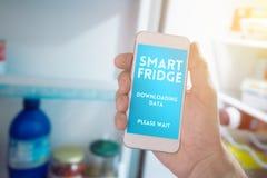 Internet de cosas, smartphone que conecta con el refrigerador fotografía de archivo