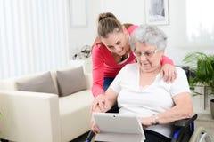 Internet de enseñanza de la chica joven alegre con la tableta del ordenador y tiempo de la distribución con una vieja mujer mayor Imágenes de archivo libres de regalías
