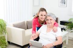 Internet de ensino da moça alegre com tabuleta do computador e tempo da partilha com uma mulher superior idosa na cadeira de roda Imagem de Stock