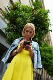 Internet de la ojeada de la muchacha del estudiante en el teléfono móvil Fotos de archivo libres de regalías