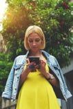Internet de la ojeada de la muchacha del estudiante en el teléfono móvil Foto de archivo libre de regalías