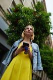 Internet de la ojeada de la muchacha del estudiante en el teléfono móvil Fotografía de archivo