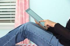 Internet de la ojeada de la persona usando una tableta y un wifi Foto de archivo libre de regalías