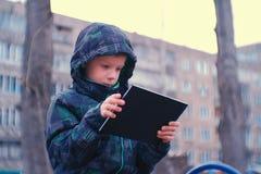 Internet de la ojeada del muchacho en su tableta que se sienta en el banco adentro en la yarda en el patio Foto de archivo