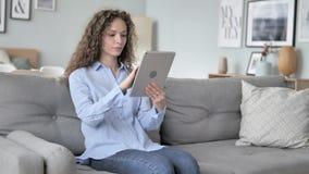 Internet de la ojeada de la mujer del pelo rizado en la tableta metrajes