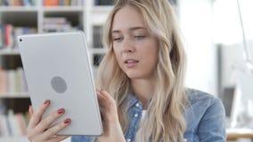 Internet de la ojeada de la mujer joven en la tableta almacen de video