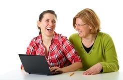 Internet de la resaca de la madre y de la hija usando la computadora portátil Imagen de archivo libre de regalías
