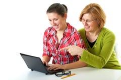 Internet de la resaca de la madre y de la hija usando la computadora portátil Imagen de archivo