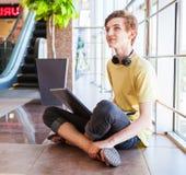 Internet de la resaca del muchacho del adolescente en centro comercial moderno Fotografía de archivo libre de regalías