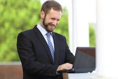 Internet de trabajo feliz de la ojeada del hombre de negocios en un ordenador portátil al aire libre Foto de archivo libre de regalías