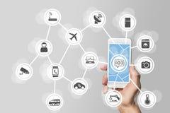 Internet del concepto de las cosas (IOT) ilustrado por el smartphone moderno que maneja objetos conectados imagen de archivo
