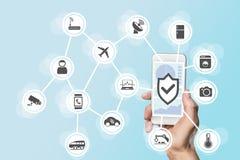 Internet des Sachensicherheitskonzeptes mit der Hand, die modernes intelligentes Telefon hält, um Eindringlinge in ein Netz von G Stockfotos