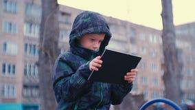 Internet di lettura rapida del ragazzo sulla sua compressa che si siede sul banco dentro nell'iarda sul campo da giuoco archivi video