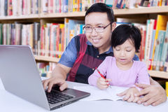 Internet di lettura rapida dell'uomo mentre insegnando ad uno studente Immagine Stock Libera da Diritti