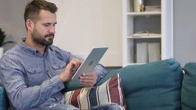 Internet di lettura rapida dell'uomo sul PC della compressa, sedentesi sullo strato stock footage