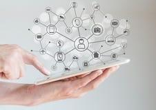 Internet do conceito das coisas (IoT) com as mãos masculinas que guardam a tabuleta ou o grande telefone esperto