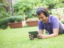 Internet dos fones de ouvido da tabuleta do homem Fotos de Stock Royalty Free