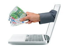 Internet earnings concept. Hand with money coming out from laptop screen stock photos