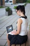 Internet en sociaal media concept - meisje in school het eenvormige gebruiken stock afbeelding
