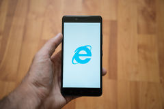 Internet Explorer logo on smartphone screen. London, United Kingdom, june 5, 2017: Man holding smartphone with Internet Explorer logo on the screen. Laminate Royalty Free Stock Image