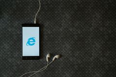 Internet explorer logo on smartphone screen. Los Angeles, USA, october 23, 2017: Internet explorer logo on smartphone screen and earphones plugged in on metal Royalty Free Stock Photo