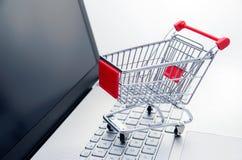 internet för begrepp 3d framför shopping Korg på bärbar datortangentbordet Royaltyfri Fotografi