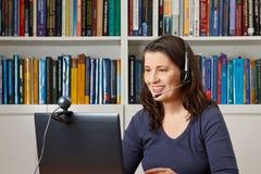 Internet för hörlurar med mikrofon för kvinnaviewphonedator fotografering för bildbyråer