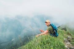 Internet fatigué de lecture rapide d'homme de randonneur utilisant le smartphone appréciant le fond nuageux de vallée marchant pa photos libres de droits