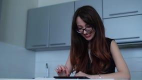 Internet feliz de la ojeada de la mujer en la tableta que se sienta por la tabla en cocina metrajes