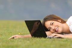 Internet feliz de la ojeada de la mujer en un ordenador portátil en la hierba Fotografía de archivo