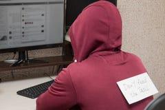 Internet fiska med drag i sammanträde på datoren Man med en inskrift på hans tillbaka matning för `-universitetslärare` t fiska m Royaltyfri Foto
