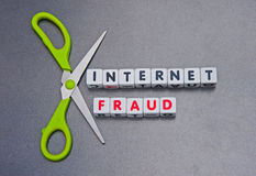 Internet fraud. Scissors around text  internet fraud  in uppercase letters inscribed on small white cubes , gray or silver background Royalty Free Stock Image