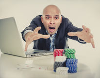 Internet gambling addict businessman on computer loosing lots of money betting on poker game Royalty Free Stock Photos