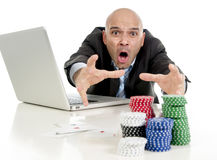 Internet gambling addict businessman on computer loosing lots of money betting on poker game. Desperate addict businessman on computer laptop loosing lots of Stock Photo