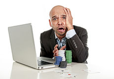 Internet gambling addict businessman on computer loosing lots of money betting on poker game. Desperate addict businessman on computer laptop loosing lots of Royalty Free Stock Photos
