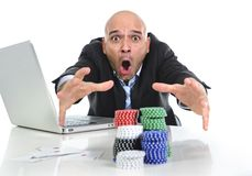 Internet gambling addict businessman on computer loosing lots of money betting on poker game. Desperate addict businessman on computer laptop winning and loosing Stock Photo