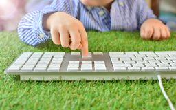 Internet gaming and education concept. Baby and computer keyboard on a green artificial grass. royalty free stock images
