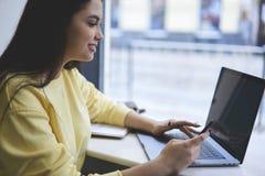 Internet giovane di lettura rapida della ragazza dei pantaloni a vita bassa tramite netbook portatile e smartphone moderno che si Fotografia Stock
