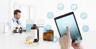 Internet healthcare and medical on mobile devices consultation, hand touch screen on digital tablet with symbols, doctor at desk. Office with pills, drugs and royalty free stock photo