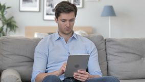Internet hermoso de la ojeada del hombre joven en la tableta metrajes