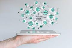 Internet industrial del concepto de las cosas IOT Mano masculina que sostiene el teléfono o la tableta elegante moderno Imagenes de archivo
